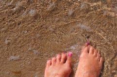 Kvinnlig fot i sandhavet, fot i vatten Royaltyfri Foto