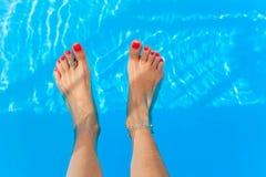 Kvinnlig fot i simbassäng Arkivbild