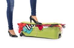 Kvinnlig fot i skor på en resväska Fotografering för Bildbyråer