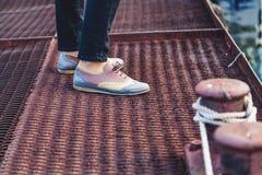 Kvinnlig fot i skor som står på pir Arkivbild