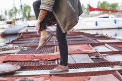 Kvinnlig fot i trendig byxa och skor på pir Arkivfoton
