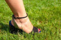 Kvinnlig fot med den svarta sandalen arkivbild