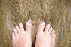 Kvinnlig fot med härlig pedikyr på sanden Rörande hav Wate Royaltyfria Bilder