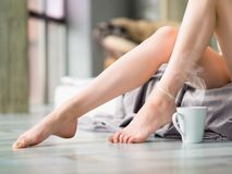 Kvinnlig fot och en kopp te eller ett kaffe Royaltyfri Fotografi