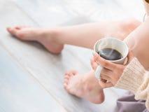 Kvinnlig fot och en kopp te eller ett kaffe Arkivfoton