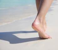 Kvinnlig fot på den tropiska sandstranden. Gå för ben. Arkivbilder