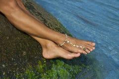 Kvinnlig fot på den våta stenen och armbandet på ankeln Fotografering för Bildbyråer