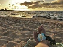 Kvinnlig fot på sandsithen en hawaiibo, blommamusikband arkivfoton