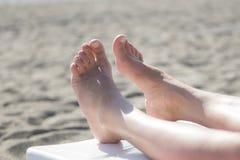 Kvinnlig fot på den sandiga stranden Arkivfoton