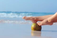 Kvinnlig fot propped på kokosnöten på havsbakgrund Arkivbilder