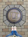 Kvinnlig fot som bär gymnastikskor som framme står av den typiska dekorerade manhålet av Kobe City, Japan arkivbild