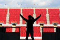 Kvinnlig fotbollsfan bakifrån i en tom stadion Arkivfoton