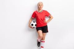 Kvinnlig fotbollspelare i en röd ärmlös tröja och svarta kortslutningar Royaltyfri Foto