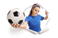 Kvinnlig fotbollspelare som bryter till och med papper arkivbild