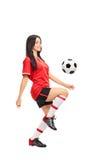 Kvinnlig fotbollspelare som jonglerar en boll Royaltyfri Fotografi