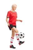 Kvinnlig fotbollspelare som jonglerar en boll och le Royaltyfria Bilder