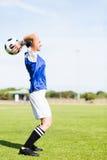 Kvinnlig fotbollsspelare omkring som kastar en fotboll arkivbild