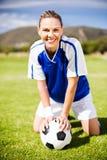 Kvinnlig fotbollsspelare som knäfaller på fält med bollen arkivfoto