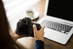 Kvinnlig fotograf med kameran på hennes skrivbord arkivfoton