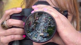 Kvinnlig fotograf som fotograferar i stadens centrum trafik lager videofilmer