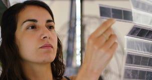 Kvinnlig fotograf som kontrollerar filmremsor på fotostudion 4k lager videofilmer