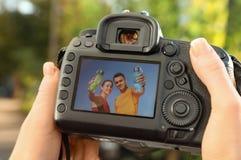Kvinnlig fotograf som utomhus rymmer den yrkesmässiga kameran med bilden på skärmen royaltyfri foto