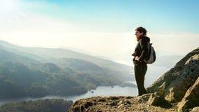 Kvinnlig fotvandrare överst av berget som tycker om dalsikt Arkivbilder