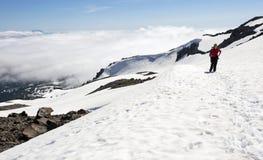 Kvinnlig fotvandrare ovanför molnen på snöig bergöverkant Arkivfoto