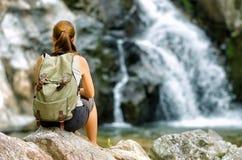 Kvinnlig fotvandrare som ser vattenfallet Fotografering för Bildbyråer