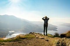 Kvinnlig fotvandrare överst av berget som tycker om dalsikt Arkivfoton