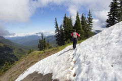 Kvinnlig fotvandrarekorsning snö på bergöverkant Royaltyfri Bild