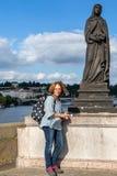 Kvinnlig fotvandrareturist som poserar bredvid en staty på Tjeckien för Charles bro I Prague arkivbilder