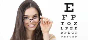 Kvinnlig framsida för leende med anblickar på synförmågaprovdiagram fotografering för bildbyråer
