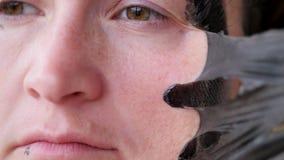 Kvinnlig framsida som täckas med en svart maskering Ta bort den rengörande filmen från huden arkivfilmer