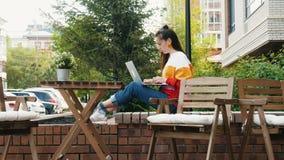 Kvinnlig freelancer som arbetar med bärbara datorn i utomhus- kafé arkivfilmer