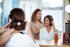 Kvinnlig frisör och flicka som ler att se i spegel i skönhetsalong arkivbilder