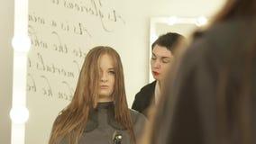 Kvinnlig frisör som kammar långt hår med hårborsten under klipp i friseringsalong Slut upp frisördanande arkivfilmer