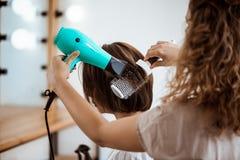 Kvinnlig frisördanandefrisyr till brunettflickan i skönhetsalong fotografering för bildbyråer