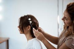 Kvinnlig frisördanandefrisyr till brunettflickan i skönhetsalong royaltyfria bilder