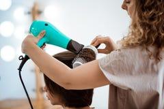 Kvinnlig frisördanandefrisyr till brunettflickan i skönhetsalong arkivbild