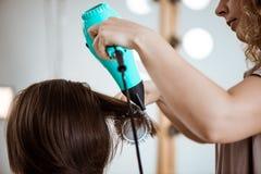 Kvinnlig frisördanandefrisyr till brunettflickan i skönhetsalong arkivfoto