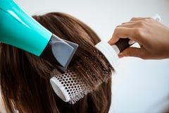 Kvinnlig frisördanandefrisyr till brunettflickan i skönhetsalong royaltyfria foton