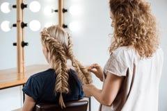 Kvinnlig frisördanandefrisyr till den blonda flickan i skönhetsalong arkivbild