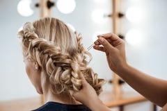 Kvinnlig frisördanandefrisyr till den blonda flickan i skönhetsalong fotografering för bildbyråer