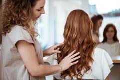 Kvinnlig frisördanandefrisyr till rödhårig manflickan i skönhetsalong royaltyfri fotografi