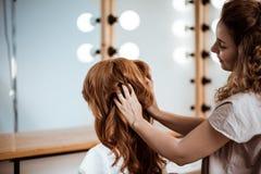 Kvinnlig frisördanandefrisyr till rödhårig manflickan i skönhetsalong royaltyfri bild