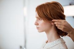Kvinnlig frisördanandefrisyr till rödhårig manflickan i skönhetsalong arkivbilder