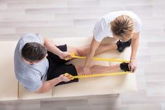 Kvinnlig fysioterapeut Giving Exercise Treatment royaltyfri bild