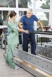 Kvinnlig fysioterapeut Motivating Senior Man som går mellan medeltalen royaltyfria foton