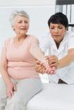 Kvinnlig fysioterapeut som undersöker en hög patienthand arkivfoto